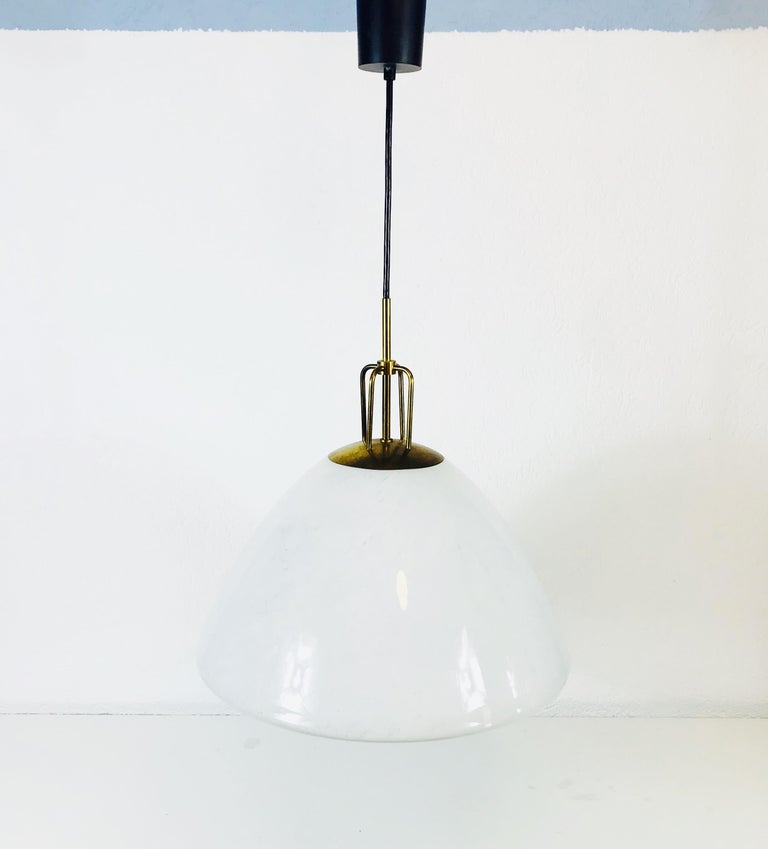 Ceiling lamp by Glashütte Limburg made in Germany in the 1960s. It is fascinating with its opaline glass, which is typical for the German brand. The shape of the lamp is similar to a cone. The top of the light is made of brass.  The light requires