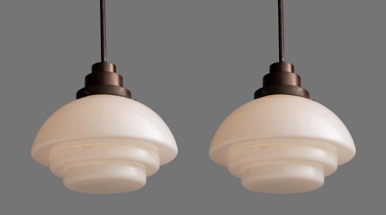 Opaque deco ceiling lights.  England circa 1930  Tiered opaline glass shades with copper fitter and rod.