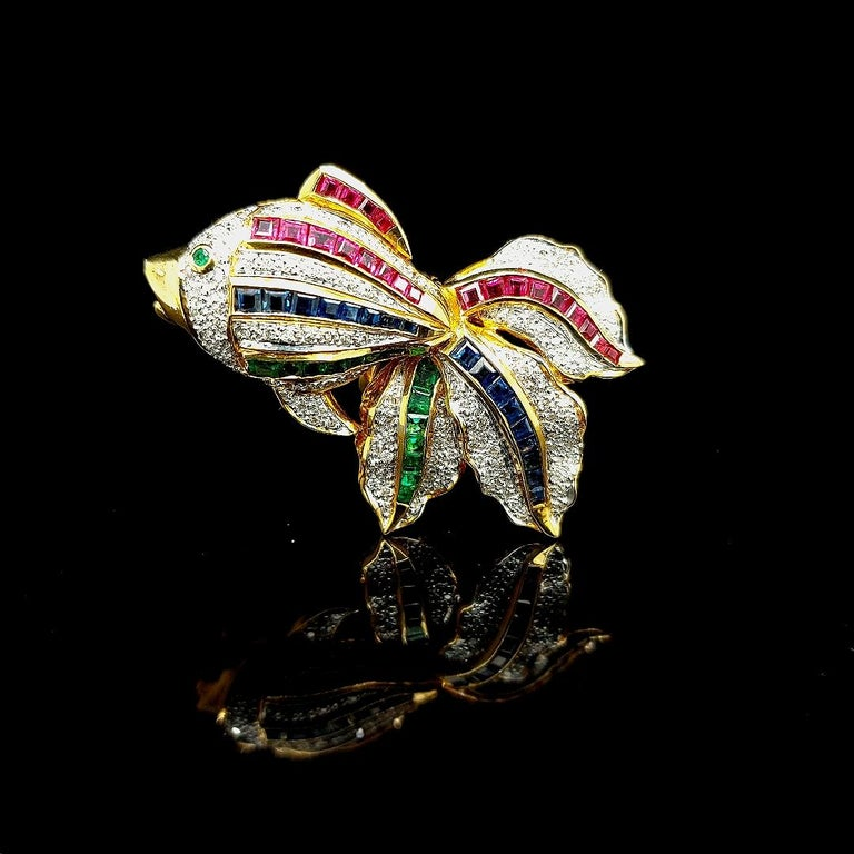Open Mouth Fish Brooch / Pendant Set With Diamonds, Ruby , Sapphire, Emerald   Attached to the jewel is a hinge to be used as a pendant when wanted.  Diamonds: 133 brilliant cut diamonds ,ca. 0,66 ct  Ruby: 21 square cut rubies ca. 1,05