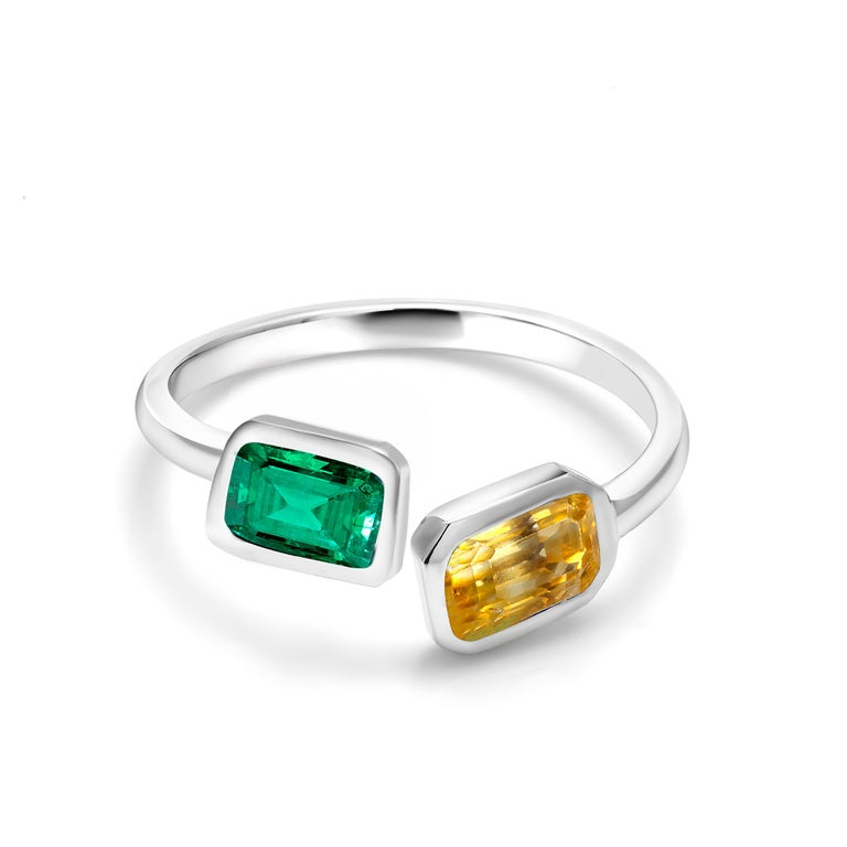 Fourteen karat white gold open shank bezel set cocktail ring Emerald cut shape emerald measuring 7x5 millimeter and weighing 0.65 carat Emerald cut yellow sapphire measuring 7x5 millimeter and weighing 0.95 carat Ring size 6 New Ring Ring can be