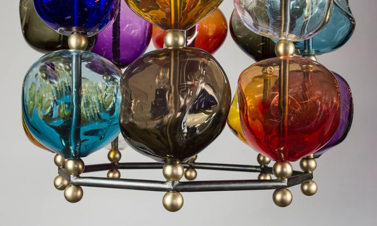 A fresh expression of the Classic lantern created to accentuate the shimmering light, which reflects in the many contours of the glass. The hand blown glass orbs with their asymmetrical shapes are assembled on an octagonal gunmetal steel frame