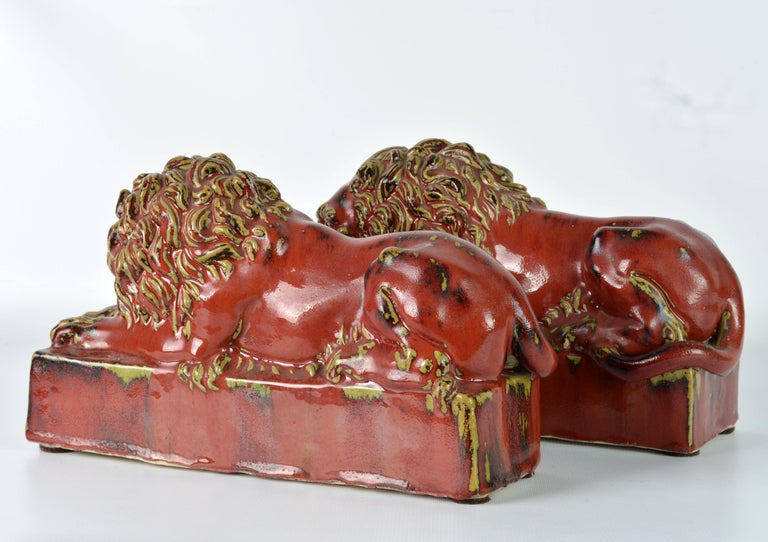 European Opposing Pair of 20th Century Oxblood and Celadon Glazed Ceramic Resting Lions For Sale