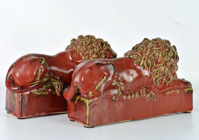 Opposing Pair of 20th Century Oxblood and Celadon Glazed Ceramic Resting Lions In Excellent Condition For Sale In Ft. Lauderdale, FL