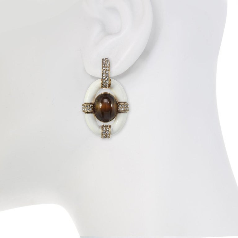 A classic CINER design, these door knocker earrings have crystal velvet encrusted accents and gorgeously hand applied enamel.  Materials:  Pewter  18K Gold Plating  Crystal Velvet Rhinestones  Clip Backing  Dimensions:  Length: 2