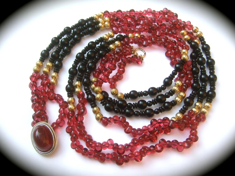 Opulent long glass beaded triple strand statement necklace c 1980s The elegant opera length necklace is comprised of a collection deep berry color smooth oval irregular shaped translucent beads; juxtaposed with rows of jet black beads in various