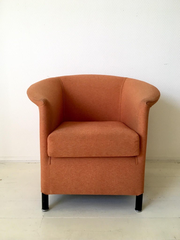 Circular forms combined with straight, this elegant armchair was designed by Paolo Piva for Wittmann, Austria. The chair features an orange and yellow upholstery and black feet with a silver colored ring. At the back a futuristic decoration with a