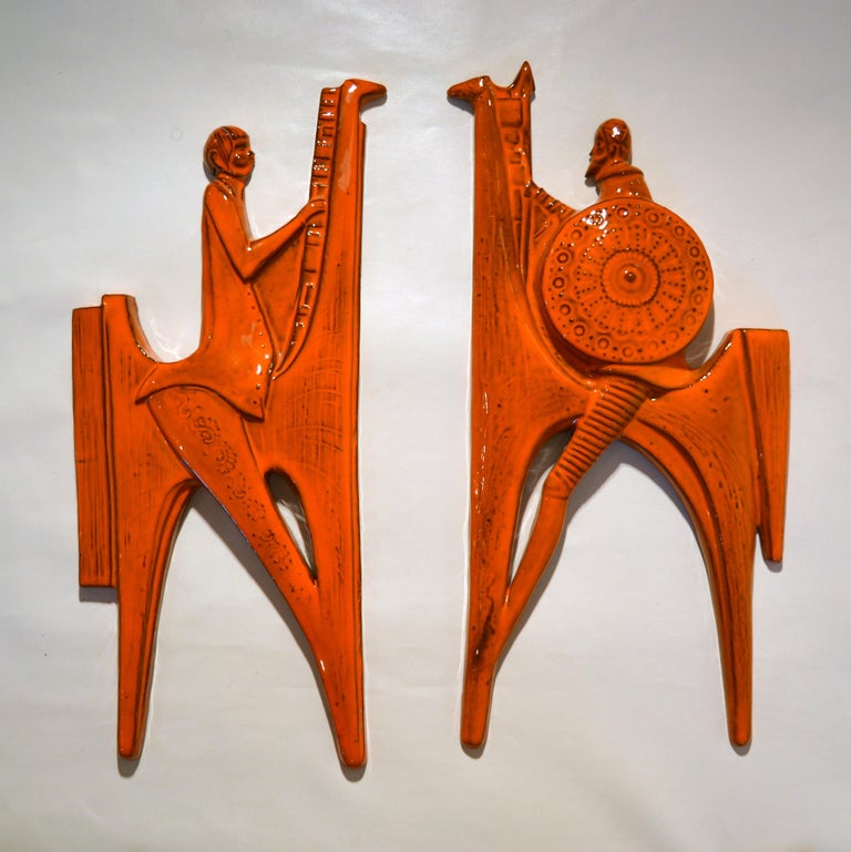 Don Quixote of La Mancha & Sancho Pancha portrayed in wall reliefs made in ceramic and glazed bright orange, 1960s Spain, signed Sanchez. They make a striking wall decoration and are easy to hang.  Don Quixote is the most influential work of