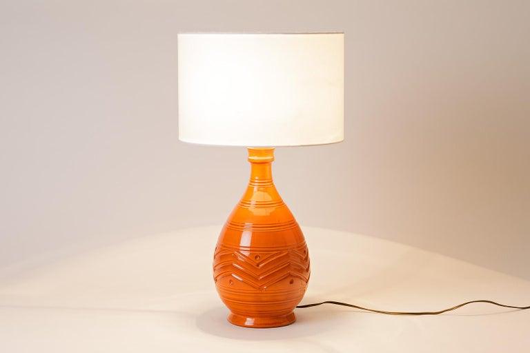 Midcentury table lamp  Shinny orange ceramic table lamp, circa 1960.  Perfect conditions.  Dimensions without lampshade : 33x17x17 with lampshade : 52x30  Sold without lampshade.