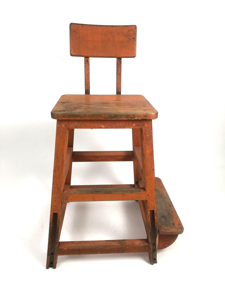 A sculptural, very sturdy and functional industrial orange painted wood and metal stool, or high chair, from a factory, circa 1920s, the curved rectangular back attached to the seat with iron bands connected to the square seat supported by 4