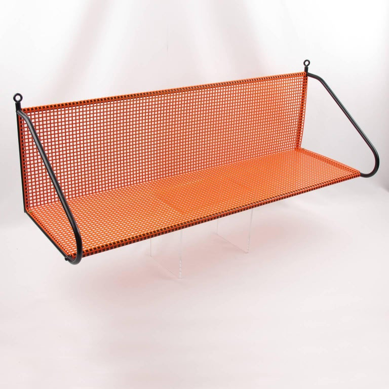 Unusual Mid-Century Modern metal shelving unit in the manner of French designer Mathieu Mategot. A striking example of French 1950s metalwork. Folded, perforated orange lacquered metal with black metal support. Measurements: 27.50 in. wide (70 cm) x