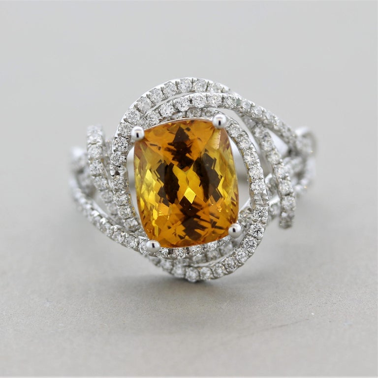 A brilliant ring featuring a GIA certified natural yellowish-orange sapphire! It weighs 4.84 carats and is free of any eye-visible inclusions allowing the stones natural brilliance and bright color to shine! It is shaped as a cushion and is accented