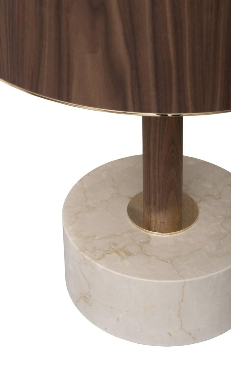 This is a classic table lamp that will enrich any interior with its unexpected, precious details. The white Botticino marble base has a simple round shape that coordinates harmoniously with the drum shape of the Canaletto walnut lampshade, adding