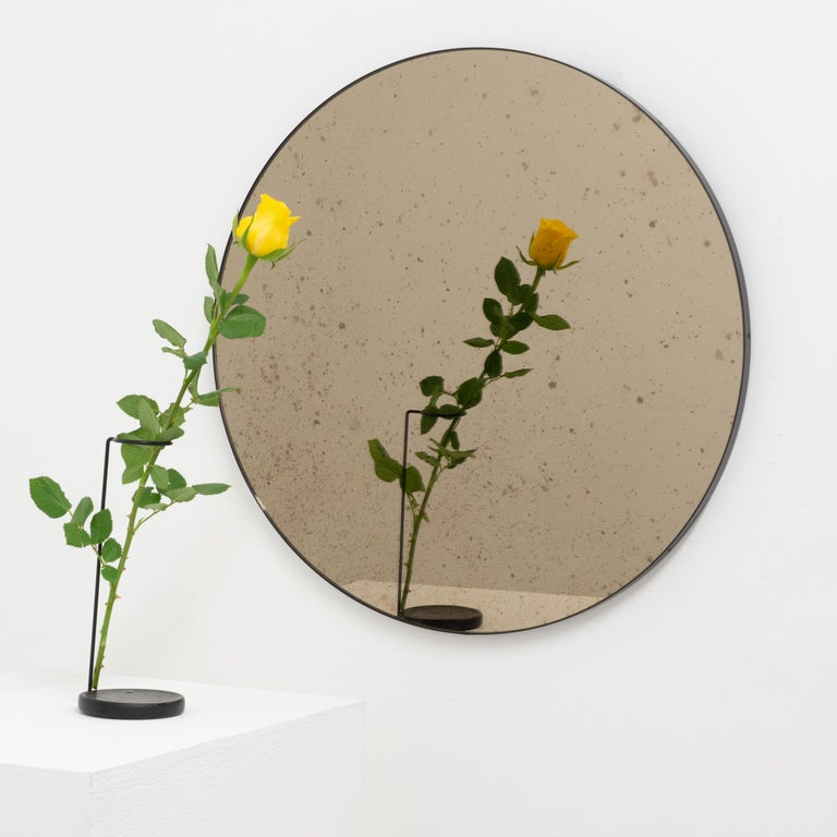Delightful bronze tinted antiqued round mirror with an elegant black frame. Designed and handcrafted in London, UK.  Fitted with a brass hook or an aluminium z-bar depending on the size of the mirror. Also available on demand with a split batten