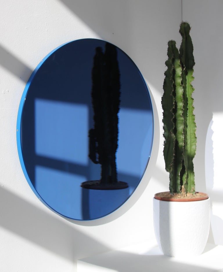 Delightful handcrafted blue tinted round mirror with a funky blue frame.