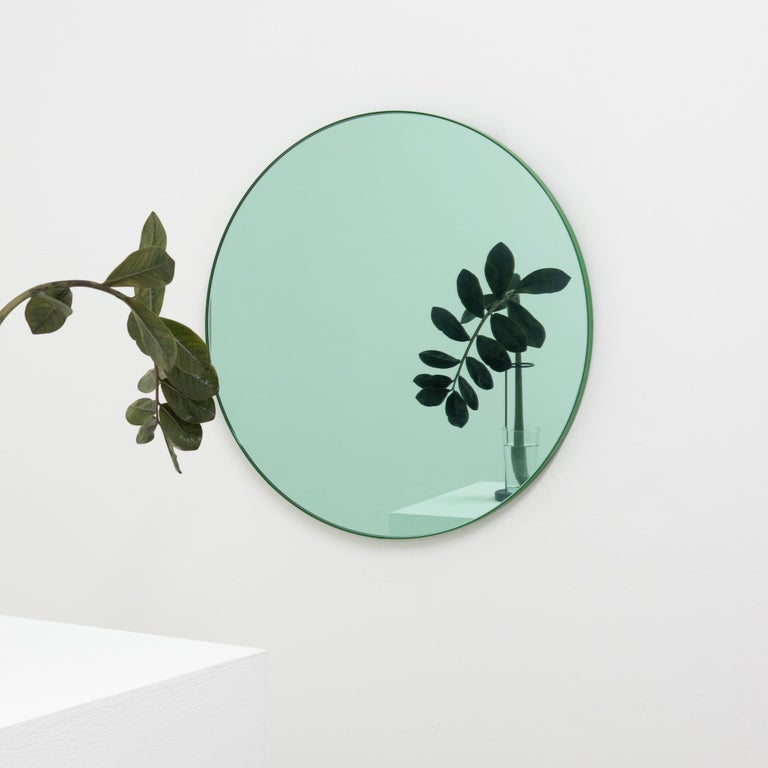 Delightful round green tinted mirror with a colorful green powder coated aluminium frame.  Designed and handcrafted in London, UK. The detailing and finish, including visible brass or green screws, emphasize the craft and quality feel of the mirror,