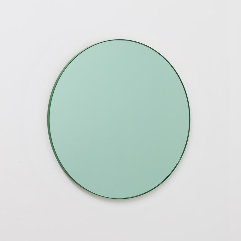 Delightful round green tinted mirror with a colorful green powder-coated aluminium frame.  Designed and handcrafted in London, UK. The detailing and finish, including visible brass screws, emphasize the craft and quality feel of the mirror, a true