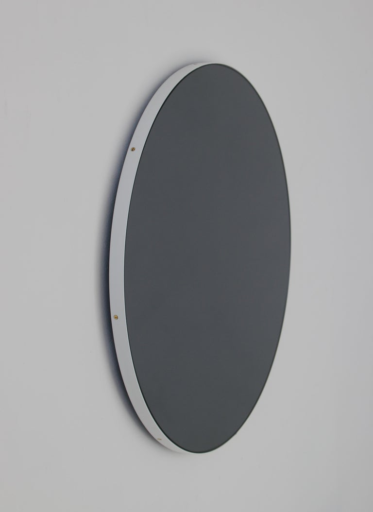 Delightful black tinted round mirror with a smart white frame. Designed and handcrafted in London, UK. The detailing and finish, including visible brass screws, emphasise the crafty and quality feel of the mirror, a true signature of our