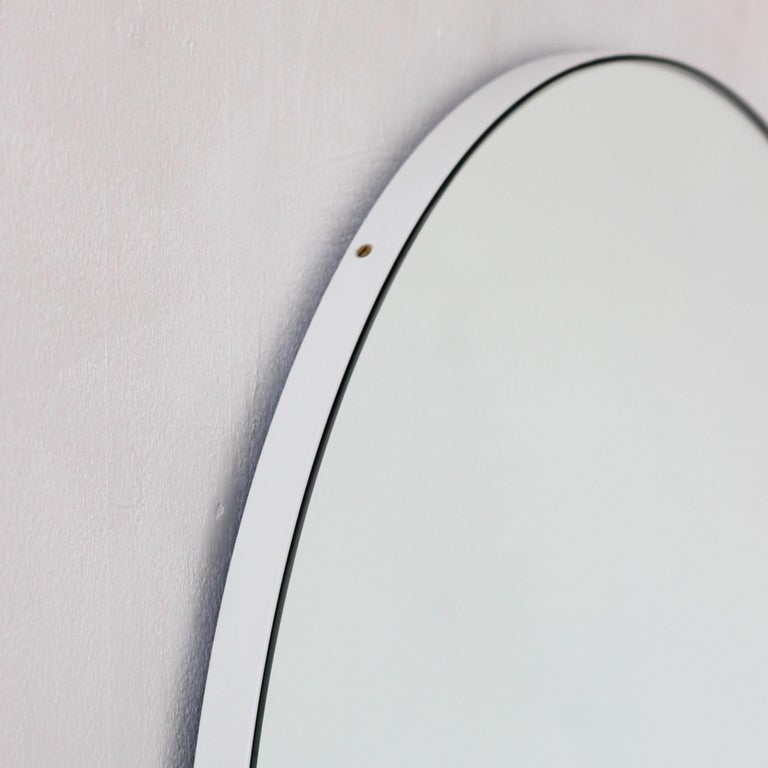 Delightful silver tinted round mirror with a smart white frame. Designed and hand-crafted in London, UK.The detailing and finish, including visible brass screws, emphasise the crafty and quality feel of the mirror, a true signature of our