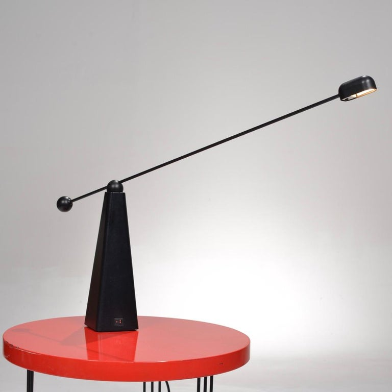 This is the orbit table lamp designed by Ron Rezek for Bieffeplast, circa 1980. Beautiful Postmodern design featuring an adjustable swivel neck and triangular base.