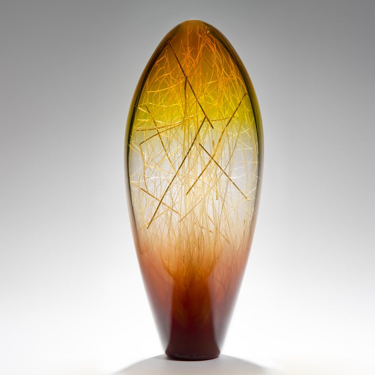 Ore in amber and coffee is a unique glass sculpture in amber, coffee and clear coloured glass by the collaborative artists Hanne Enemark (Danish) and Louis Thompson (British). The outer glass form contains a multitude of Fine white canes of glass,