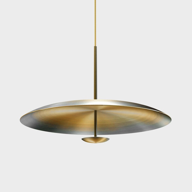 Two finely hand-spun brass plates make up this pendant light, a bronze to brass gradient accentuates the shape. The light is projected into the shade and reflects out, illuminating without creating a glare. Measures: 100 cm diameter. This light