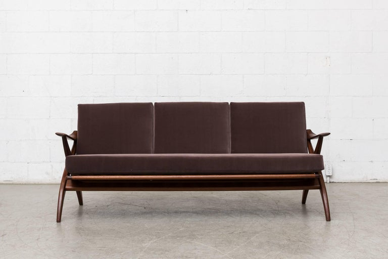 Lightly refinished teak three-seat sofa for Topform. Newly upholstered cushions in cafe grey velvet cushions. Organically carved X-frame. Elegant molded arm rests. Measures: Seat height 16.75, arm height 22.5.