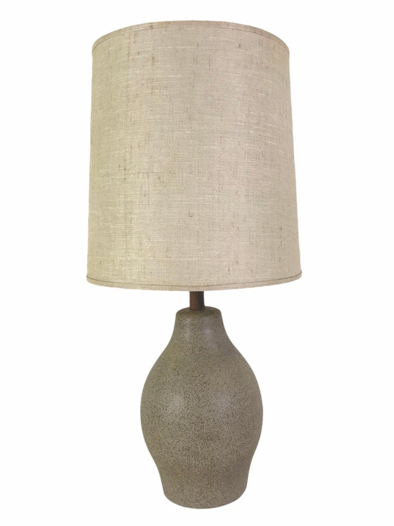 Jane & Gordon Martz for Marshall Studios Mid-Century Modern pottery table lamp. With a warm and organic speckled brown glaze over light green colored underglaze and bulbous shaped body, this great table lamp is a delight. Featuring a walnut neck and