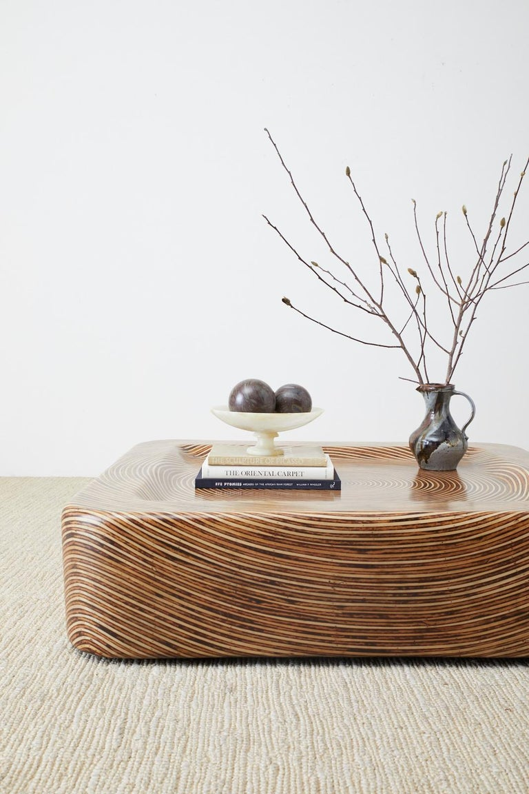 Mesmerizing organic modern cocktail or coffee table constructed from strips of bamboo rattan intricately inlaid into a geometric round design. The square form features a molded top with a depression making a wave pattern on the sides of the table.
