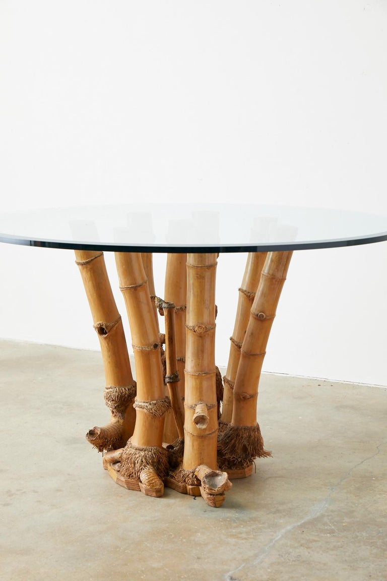 Large round glass top dining table featuring an organic modern style bamboo root base. Rare 8-leg bamboo stalks with their roots and base intact which is seldom seen usually only when the farms and trees are retired. Topped with a .75 inch thick