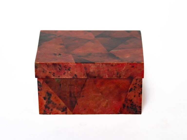 Gorgeous handcrafted box comprised of lacquered pen shell. Hand-dyed in variant hues of ruby red and black. The box has a graphic mosaic geometric design. The lid opens to reveal a palm wood interior. Makes a great jewelry box or desk accessory.