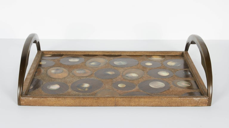 Exquisite serving tray features a variety of exotic materials and is all handcrafted. Covered in shagreen with hues of tan, and features mother of pearl inlays over palmwood insets. The combination creates a beautiful concentric and geometric
