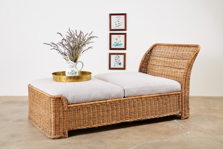 20th century wicker daybed or chaise lounge featuring a sleigh style form. Constructed from a metal frame covered with woven wicker in an organic modern style. Newly upholstered cushions and pillow with classic French blue and white ticking stripe
