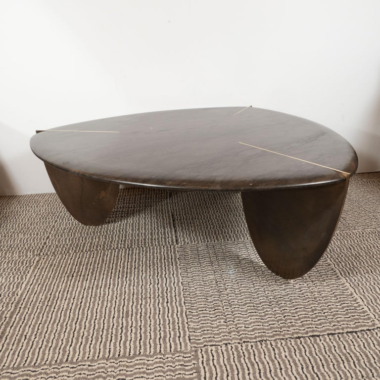 This stunning and refined organic modernist cocktail table was custom designed and fabricated in the United States by hand. It features a shield form in java hued armani marble with bowed sides that comes to three rounded points bisected by
