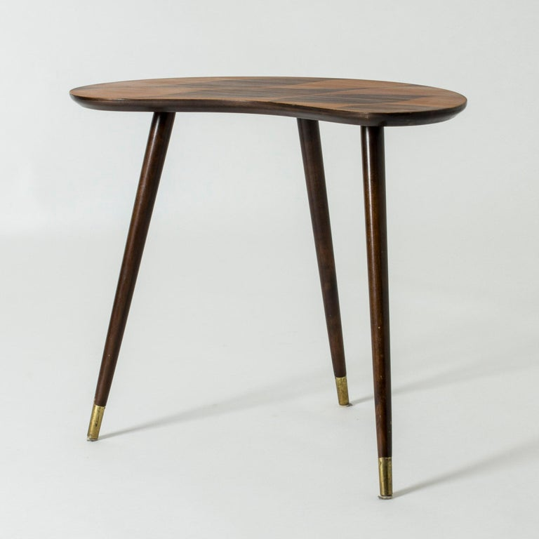 Lovely small occasional table, made in Sweden in the 1950s. Curved kidney-shaped tabletop with contrasting wood inlays in a graphic pattern. Three legs.