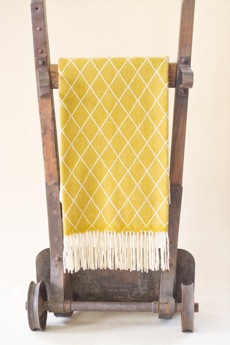 The Otilia yellow diamond pattern blanket or throw has been created by an incredible and unique family owned weaving and textile company in Portugal. This company impressed us so much by their commitment to working with the environment, their