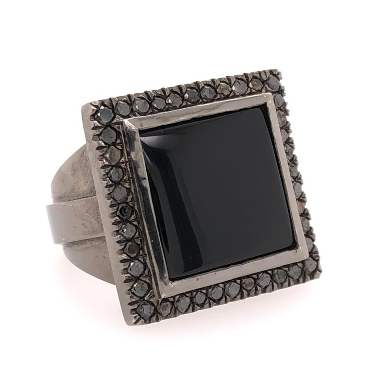 Black onyx, black diamonds, and 18K black gold. This ring is a trifecta of fashion! Go from the office to formal events with confidence.  Black Onyx surrounded by round cut black diamonds all set into a substantial 18k black gold setting.   Size: 8.5