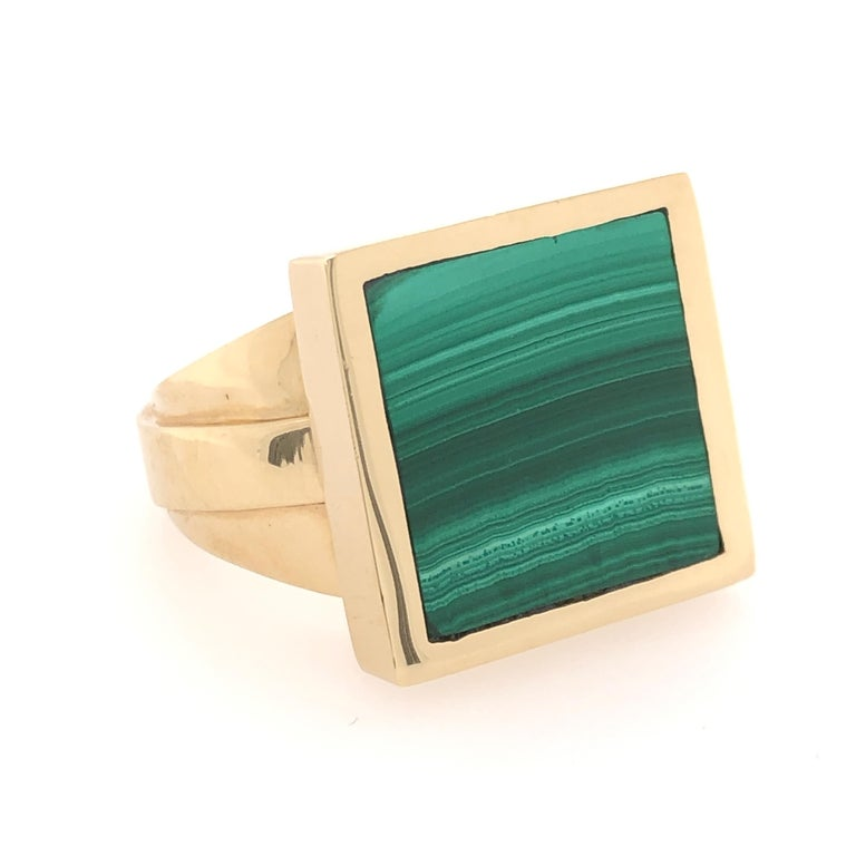Gentlemen, if you like a little bit of color with the weight of a solid, study ring this 18 karat yellow gold malachite ring is for you. The varying green values in the natural striations of the this handsome stone compliment the angular design of