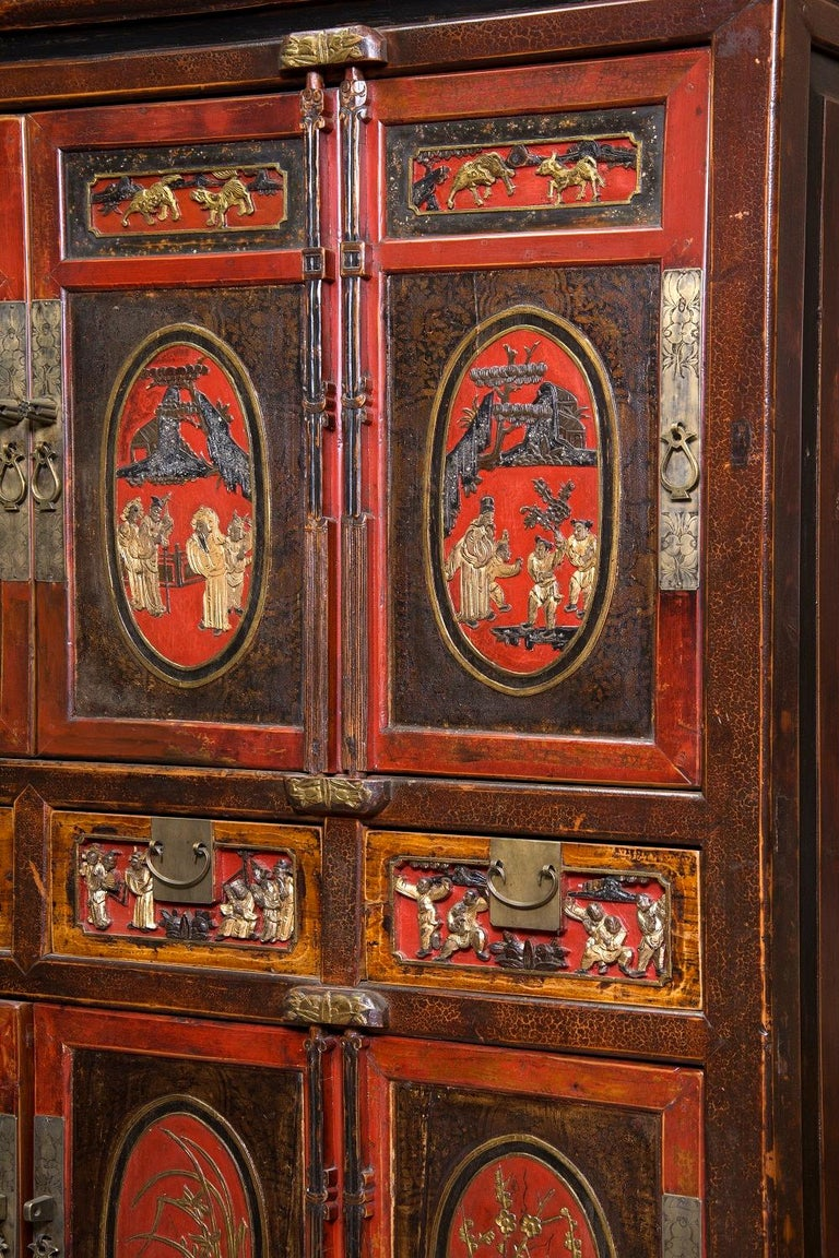 Wardrobe with two bodies with doors up and down, flanking four drawers, decorated on the front with figurative motifs of strong oriental influence and metal fittings. Both in the structure and in the decoration and the chosen colors (predominance of