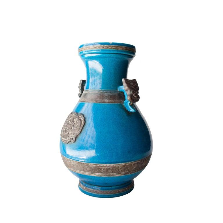 Turquoise ceramic vase with oriental motifs.