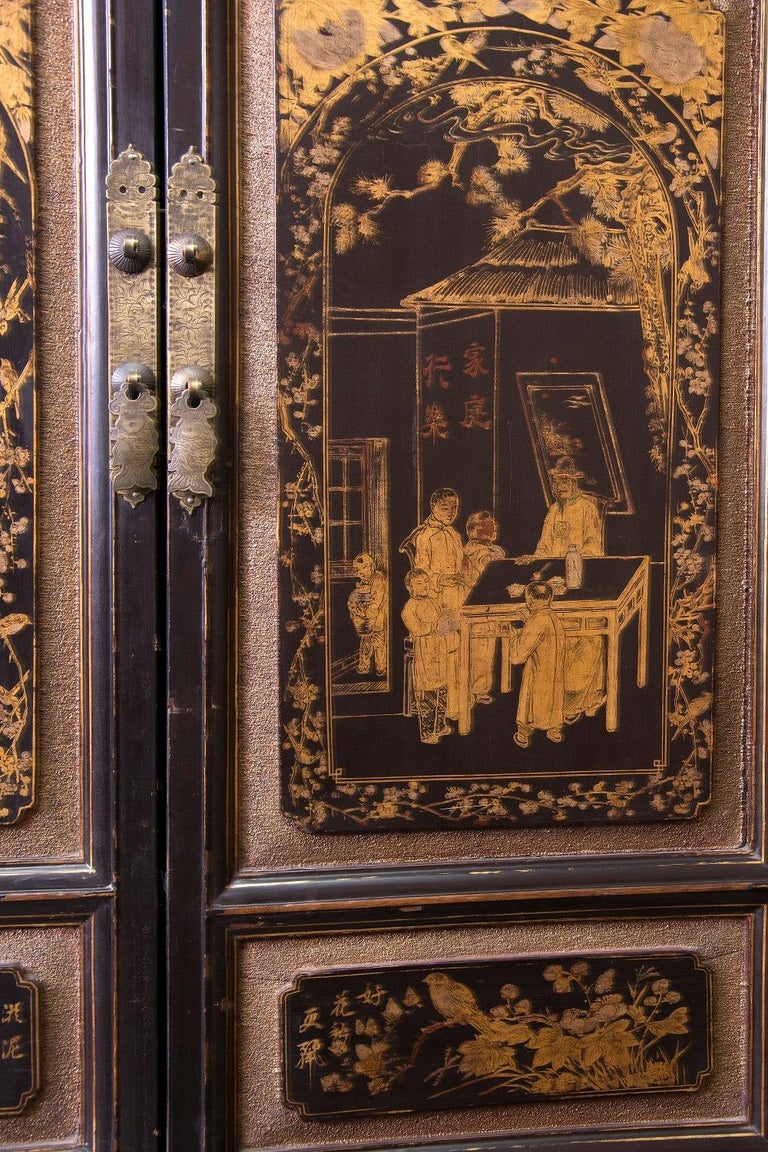 Wardrobe with two bodies, with two doors and two drawers in each (larger the upper ones), decorated on the sides with red stripes framing rectangular areas in dark tone, and, on the front, with pieces of lacquered wood with figurative scenes and