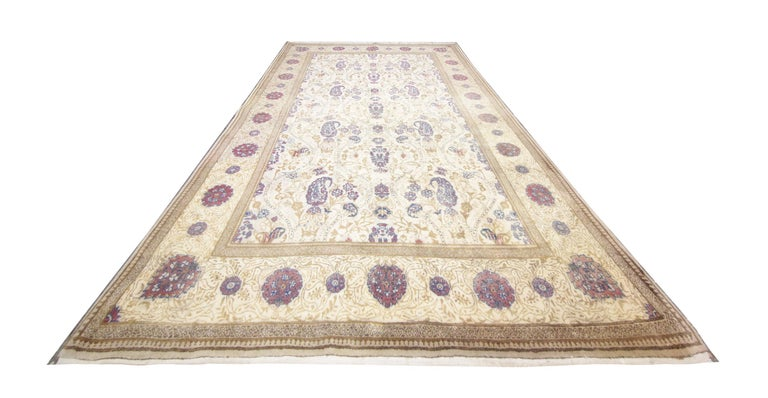 Beautifully handwoven patterns of floral and paisley designs sit on a background of cream and beige to create this stunning all-over design area rug. This vintage rug has been handmade carpet by Turkish artisans, created with handspun wool which has