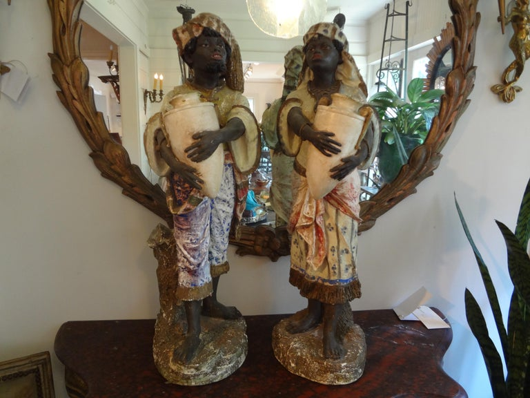 Finely detailed pair of orientalist polychromed plaster Arabesque or Moorish figures. This beautiful pair of Arabesque figures depicts a male and female in traditional Moorish clothing. These antique orientalist figures date to the 1920s.