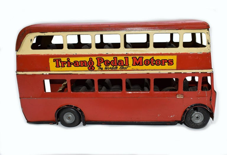 There aren't too many more iconic things to London than the red double decker bus. This is an original 1950s Triang Minic Double Decker London Bus. The colouring is vibrant and very indicative to the era, dark cream and red with advertising transfer