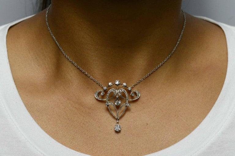 An intriguing antique Edwardian diamond necklace pendant finely handcrafted of platinum with enchanting, swirling foliate swags and garlands, typical of the French Belle Epoque era. Adorned with over 1 carat of twinkling old mine and rose cut