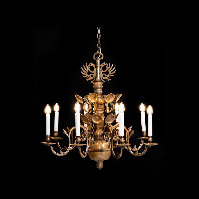 Polish baroque chandelier from the 18th century, originally for wax candles, electrified end of 19th century. Brass-body in baluster-form with pluged in blossoms, voluted arms and eagletop. Please notice the handcut screws and the varied casting and