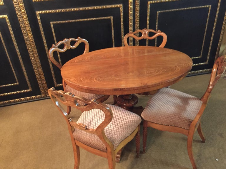 Beautiful dining table with 4 chairs original Biedermeier ashwood, circa 1850. Turned table with center column with 3 legs end in paw feet end. Chairs at the front, the legs turned and curved at the back. Backrest with beautiful ornaments.
