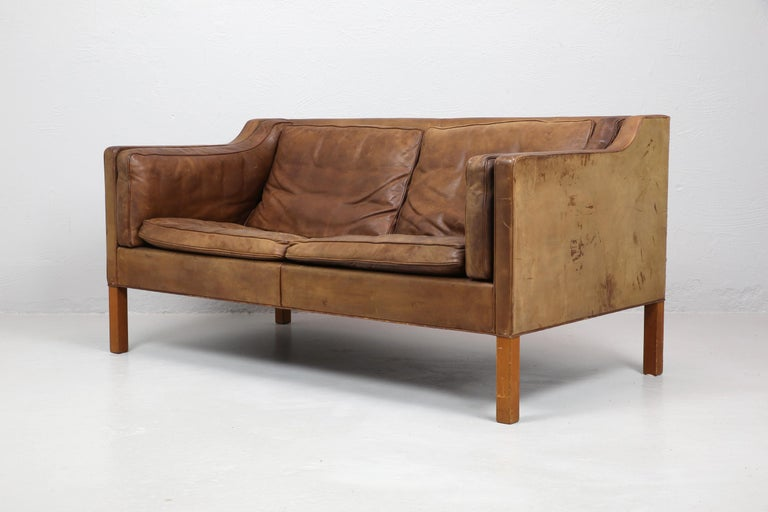 Original two-seat model 2212 sofa designed by Borge Mogensen in 1965 and made by Frederecia, Denmark. In original condition with a some wear, marks and patina to the leather. A pair are available.