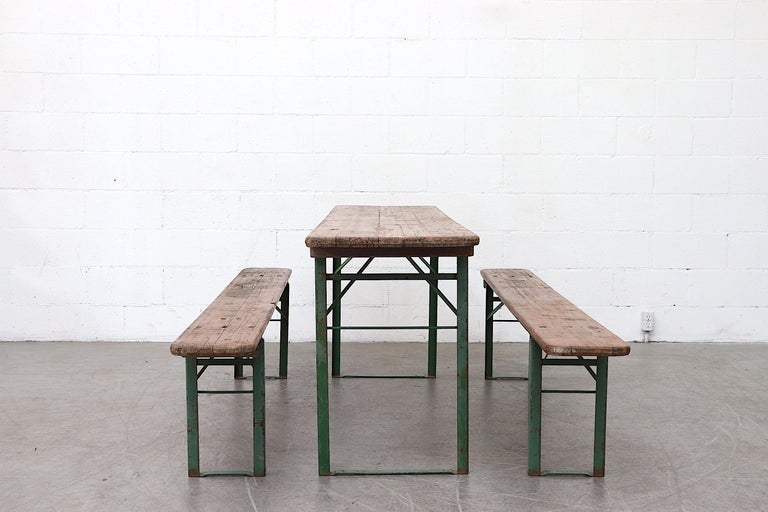 Wood topped folding tables and benches, sold as a set of 2 benches and 1 table. Metal is in original condition with visible patina. Wood in original used condition as well. Sets vary in color and wear. Benches measure 86.5 x 10.5 x 18.5. Set price.