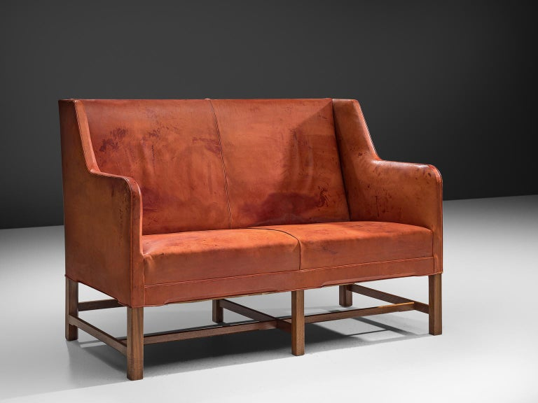 Kaare Klint for Rud Rasmussen two-seat settee, in red cognac leather and teak legs, Denmark, 1930s.  Classic and elegant Scandinavian custom made two-seat settee by Kaare Klint for manufacturer Rud Rasmussen. The piece is upholstered with patinated