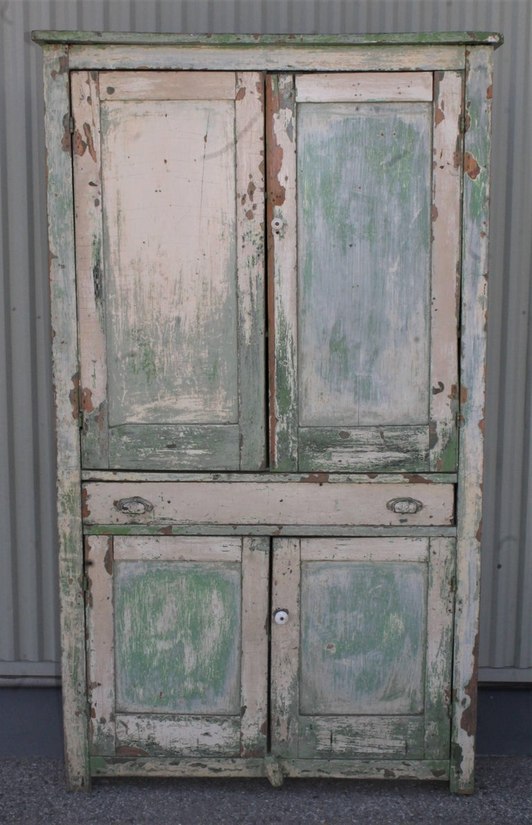 This fine funky Midwestern wall cupboard with a cream over green worn and aged painted surface. This 19th century funky four door wall cupboard is in good, worn condition. The interior is in a original apple green painted surface.